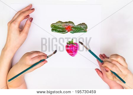 Top view child's hands draws a gouache on paper. Gouache and paper for painting and child drawing.