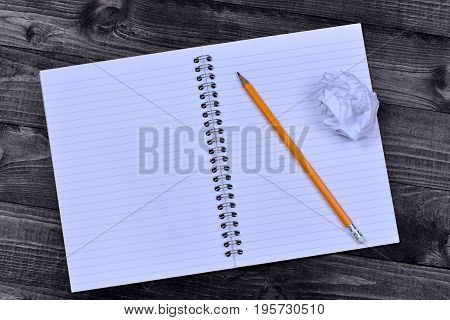 Notebook with pencil and crumpled paper on desk