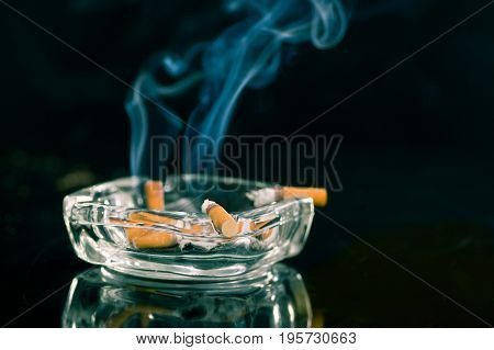 Consumed cigarettes over a crystal ashtray in black background.