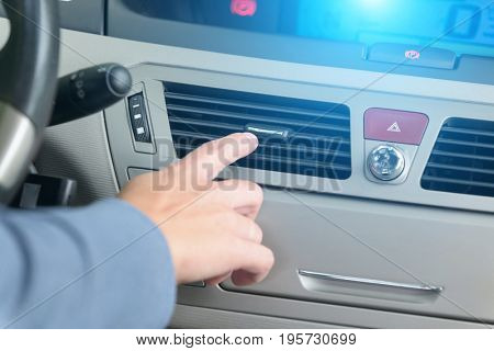 Driver hand tuning air ventilation grille, emergency flasher switch and light in modern car interior