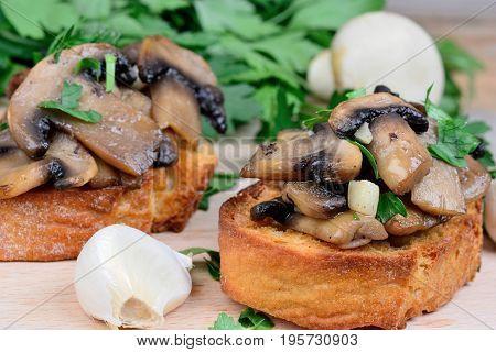 Bruschetta with mushroom garlic and parsley on table