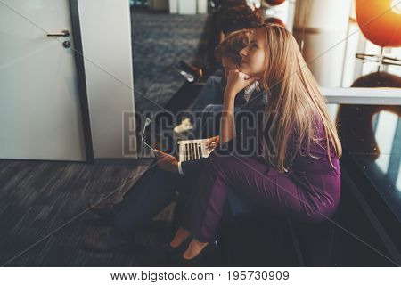 Beautiful caucasian lady in purple suit thoughtfully looking up while sitting on rung with her colleagues with laptop during brainstorm in office chillout space near mirror and window