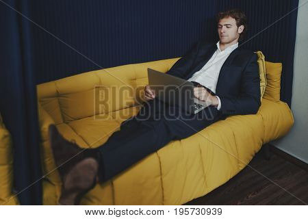 Young handsome entrepreneur with small beard in formal suite is chilling with laptop on office sofa in recreation area during coffee break
