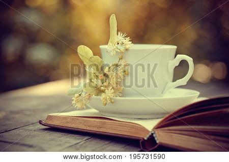 Lime tea in a white mug and the open book on a wooden table.