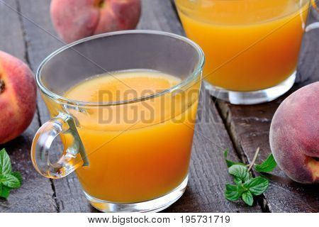 Peach juice in a glasses on wooden table