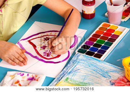 Small students painting in art school class. Child drawing by paints on table. Top view of girl in kindergarten. Creation of greeting cards for parents.