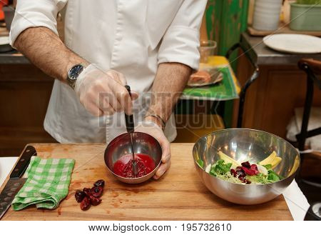 Chef is making salad dressing of red berries, oil and vinegar with whisker
