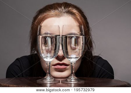 girl looks at camera through wine glasses with water toned image