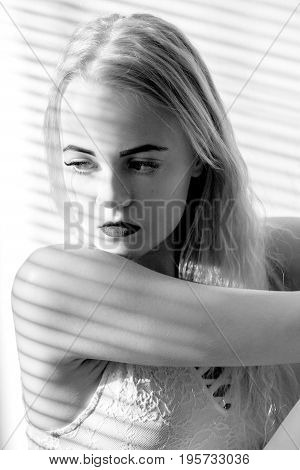 sad girl sits in sunlight with blinds monochrome