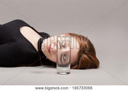 girl looks at camera through glass with water on gray background with copy space