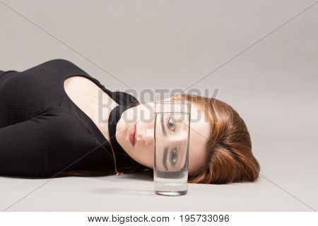 sad girl and glass with water on gray background with copy space