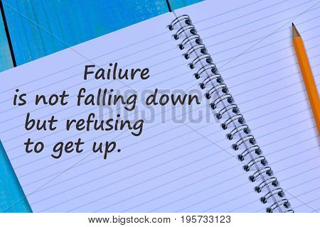 Failure is not falling down but refusing to get up text on notebook page