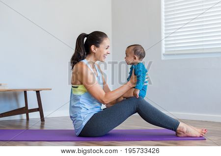 Happy woman playing with 6 months baby while doing yoga. Smiling mother doing yoga exercise with multiethnic baby while sitting on yoga mat. Little cute boy sitting on mother knee playing at home.