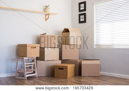 Stack of cardboard boxes in an empty room. Pile of carton boxes on the floor in an empty apartment. Stack of moving boxes in new house.