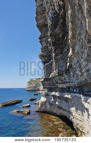 BONIFACIOFR - JUNE 21 2017 - Tourists on the narrow path carved in the cliffs below Bonifacio