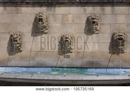A series of sculpted stone head fountains