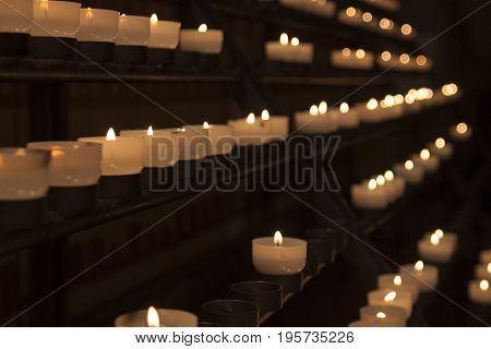 Rows of glowing prayer candles in a church
