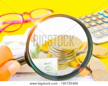 Abstract money saving. Woman's hand holding magnifying glass over coins with calculator and pink glasses on yellow background