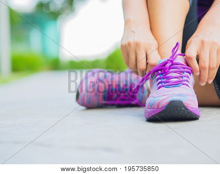 Running shoes - closeup of woman tying shoe laces. Female sport fitness runner getting ready for jogging in garden background
