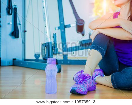Running shoes - closeup of tired woman resting after workout with fitness equipments in background