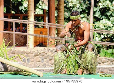 Honolulu Hawaii - May 27 2016:A young Samoan man demonstrating the art of weaving in the Village of Samoa at the Polynesian Cultural Center.
