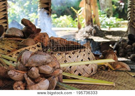 A traditional Samoan cooking area inside a hut with woven baskets and coconuts ready to prepare.
