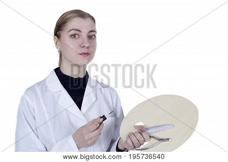 Young woman in a white coat with a manicure tool and a palette
