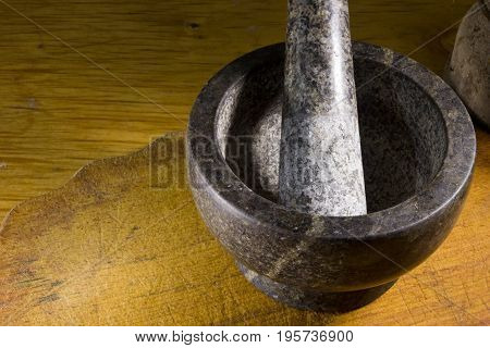 Stone mortar with a pestle on a wooden cutting board