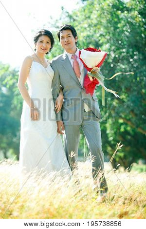 couples of bride and groom standing over meadows field