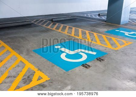 Handicap sign and yellow stripes on cement floor at parking area in perspective view. Restricted parking spot for wheelchair or disabled accessibility. Reservation is available.
