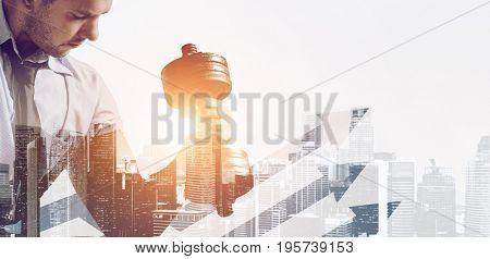 Hard working business concept. Strong businessman with dumbbell mixed with sunset city skyline