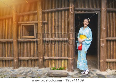 Woman wearing traditional clothing kimono in front of old wooden house outside. Japaneses sightseeing antique japan architecture Asian woman traveling on japan.