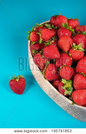 strawberries in wooden heart shaped dish on turquoise painted wood