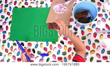 Top view of kid doing arts and crafts activity
