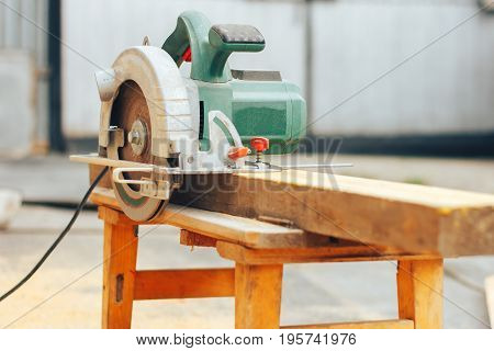 green circular power saw is standing on wooden board