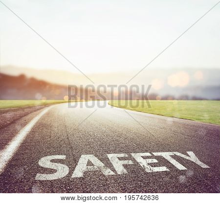 Road with safety writing on the asphalt with sun in front. Concept