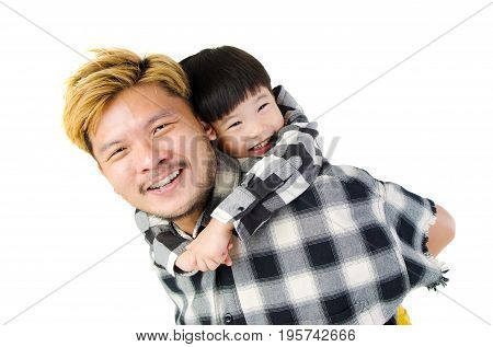 Asian father piggyback his son in the studio.