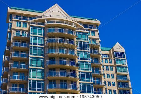 Multi Story Building With Balconies Against Blue Sky Background