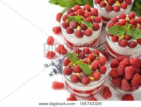 Raspberry cheesecake in a glass on a white background