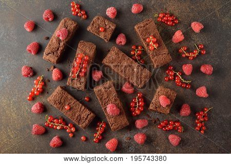 Chocolate brownies with raspberries and currants on a brown background