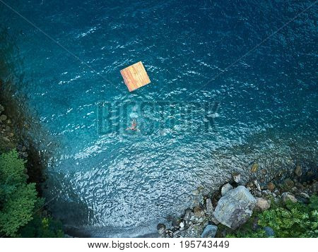 Woman swimming in blue water aerial above view. Girl swin in lagoon water top view