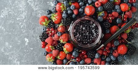 Jam from fresh forest berries on a gray background