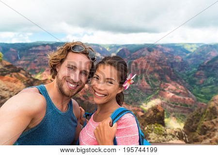 Selfie couple hikers in Waimea Canyon Hawaii hike taking self-portrait picture with camera phone having fun hiking in Kauai mountains, Hawaii. Woman and man in love taking photos on adventure travel.