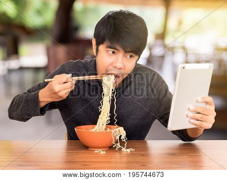 Man eating chinese noodle monstrously whilst looking and using tablet. Concept of smartphone addiction phubbing or social network issues