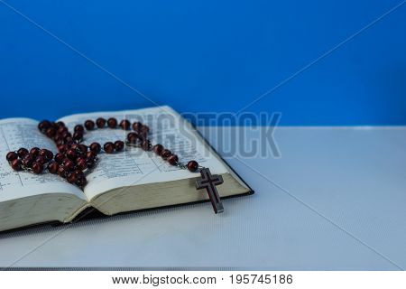 Bible and the crucifix on a table. Beautiful background.Religion concept
