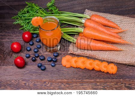 Healthy eating and dieting conceptfresh carrot and carrot juice or organic healthy juice in glass tomato fruitvegetables on a grey wooden table wall background with copy space .