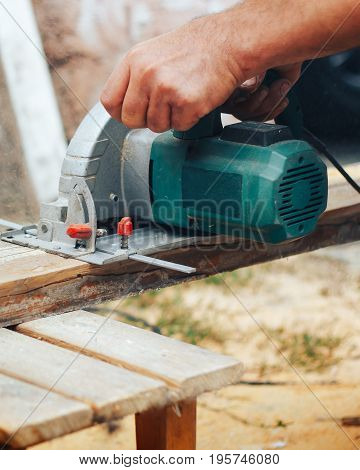 Close up electric saw to sawing wood board solf focus.