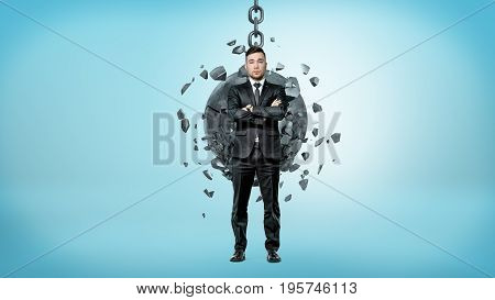 A businessman on blue background looking up over his shoulder white a wrecking ball crashes on his back. Solid business. Crisis proof employment. Insurance and protection.