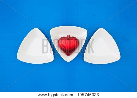 Red heart and triangular ceramic bowls for sushi on the blue wooden table