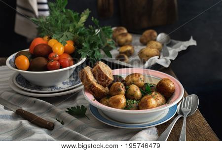 Close up plate with new fried potatoes and fresh home-made vegetables on a rustic wooden table. Dinner table concept. Dark Style